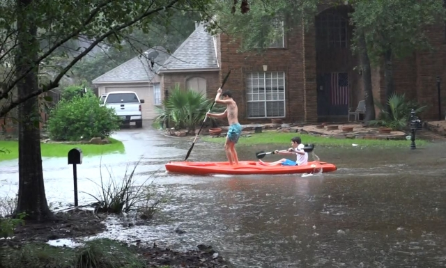 Kids kayaking in front of house during Harvey